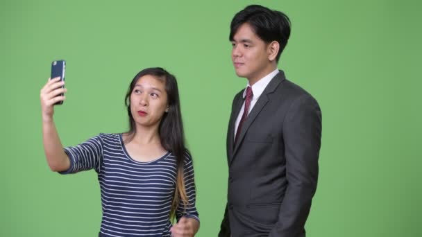 Young handsome Asian businessman and young Asian woman working together