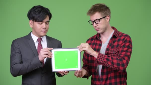 Young handsome Asian businessman and young Scandinavian businessman working together
