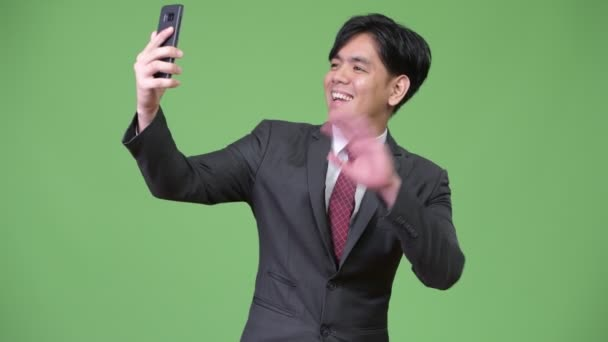 Young handsome Asian businessman using mobile phone