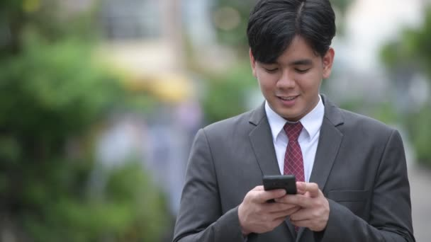 Young handsome Asian businessman using phone in the streets outdoors