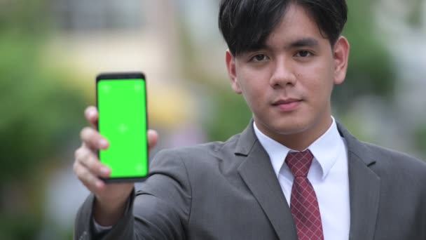 Young handsome Asian businessman showing phone in the streets outdoors
