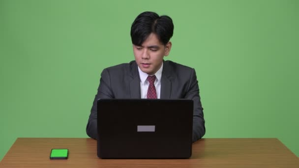 Young handsome Asian businessman working with laptop against green background