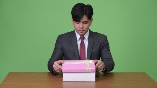 Studio shot of young handsome Asian businessman against chroma key with green background