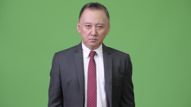 Mature angry Japanese businessman pointing at camera