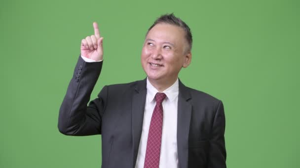 Mature happy Japanese businessman thinking while pointing finger up