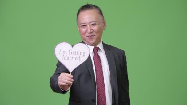 Mature Japanese businessman holding paper sign