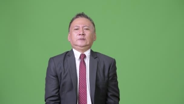 Mature Japanese businessman exercising