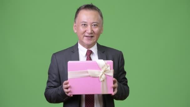 Érett japán üzletember, a zöld háttér díszdobozban