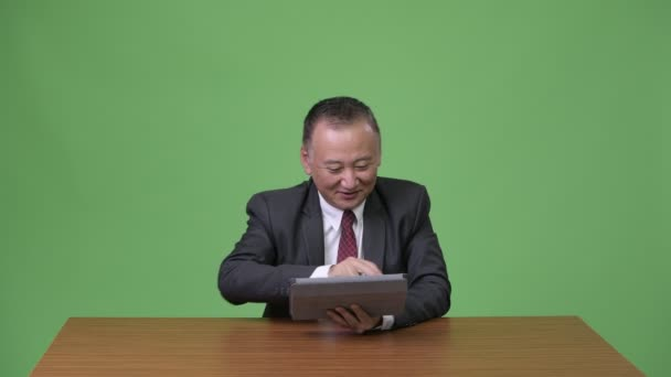 Mature Japanese businessman working with digital tablet