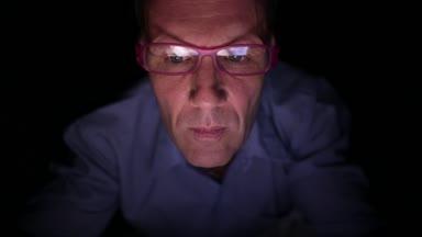 Volwassen scandinavische man met digitale tablet in de donkere