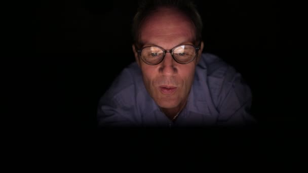 Mature Scandinavian man watching adult videos with digital tablet in dark room