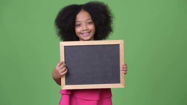 Mladý roztomilý Africká dívka s Afro vlasy drží tabule