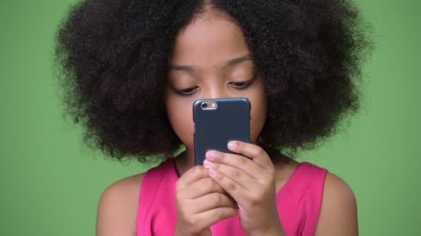 junge süße afrikanische Mädchen mit Afro-Haar mit Telefon