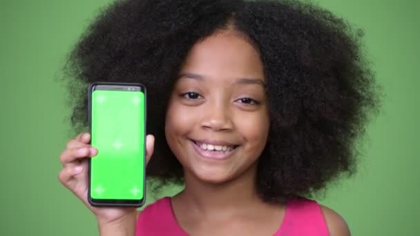 junge süße afrikanische Mädchen mit Afro-Haar zeigt Telefon