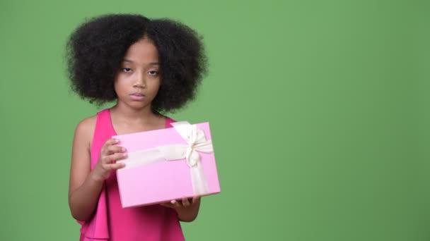 Mladý roztomilý Africká dívka s Afro vlasy drží krabičky