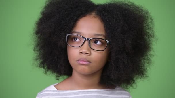 Young cute African girl with Afro hair against green background