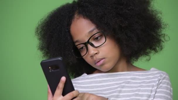 junge süße afrikanische Mädchen mit Afro-Haaren schauen schockiert, während sie telefonieren