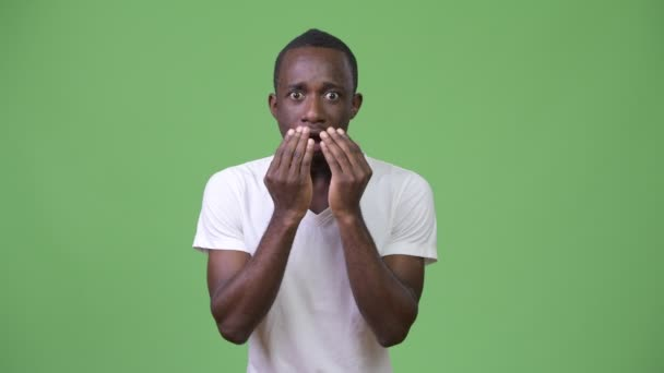 Young African man looking shocked against green background