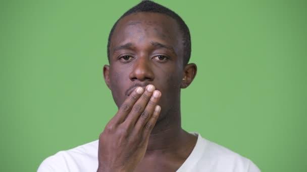Africký mladík vypadal šokován a vinu proti zeleným pozadím