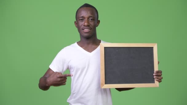Young African man showing blackboard and giving thumbs down