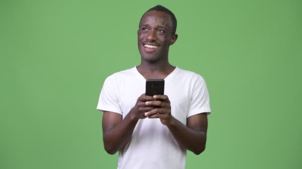 Young African man thinking while using phone against green background