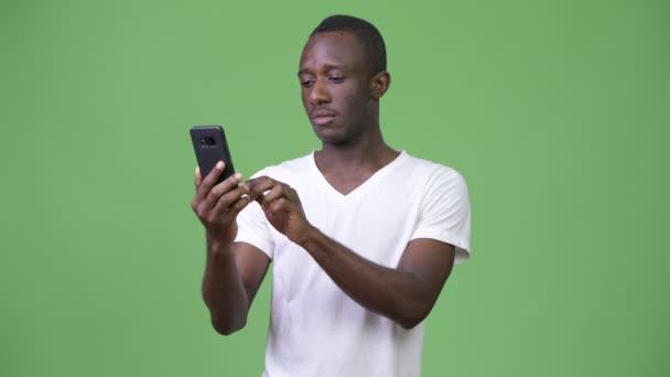 Africký mladík pomocí telefonu před zeleným pozadím