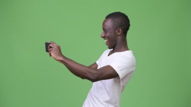 Young African man video calling with phone against green background
