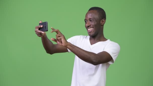 Young African man taking selfie against green background