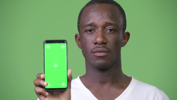 Young African man showing phone against green background