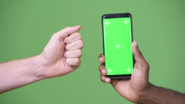 Dvě multietnické ruce ukazující telefon zároveň dává palec dolů