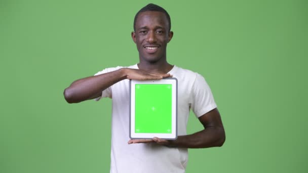 Young happy African man showing digital tablet
