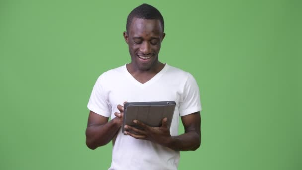 Young happy African man using digital tablet against green background