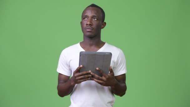 Young African man thinking while using digital tablet