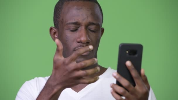 Young sad African man using phone and getting bad news