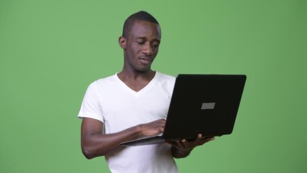 Happy africký mladík s úsměvem při používání notebooku