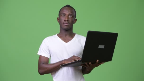 Young African man thinking while using laptop