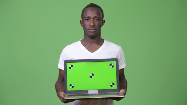 Young African man showing laptop