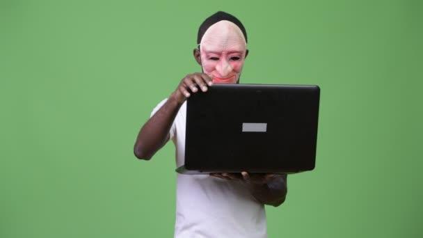 Africký mladík nosit masku a zobrazeno prostředníček při používání notebooku