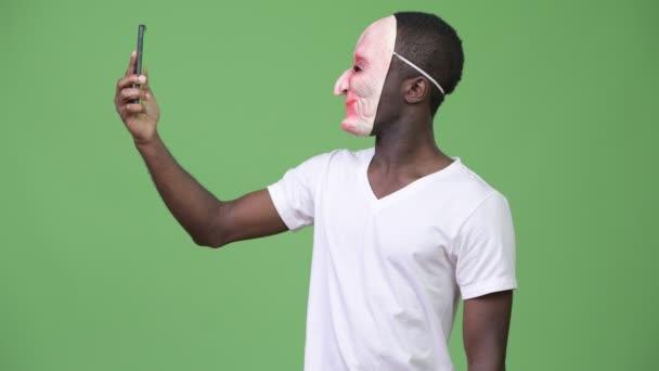 Africký mladík video volání při nošení masky a zobrazeno prostředníček