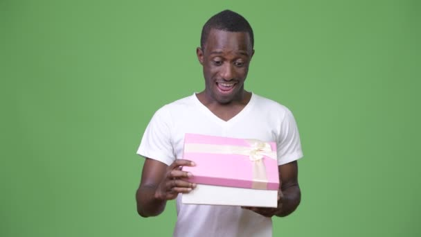Young happy African man looking surprised while opening gift box