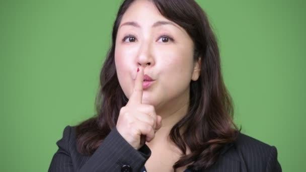Zralé krásné asijské podnikatelka s prstem na rtech