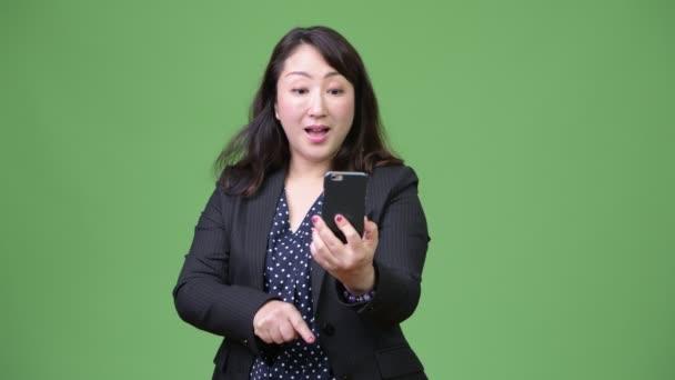 Érett gyönyörű ázsiai üzletasszony telefont, és egyre jó hír