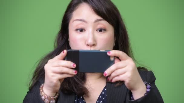 Mature beautiful Asian businesswoman using phone and looking shocked