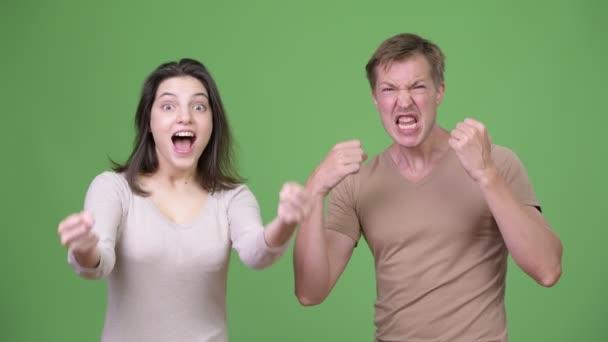 junges Paar blickt aufgeregt vor grünem Hintergrund zusammen