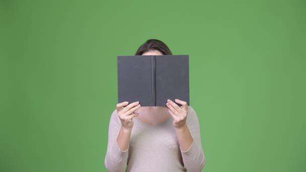 Mladá krásná žena skrývá za knihu