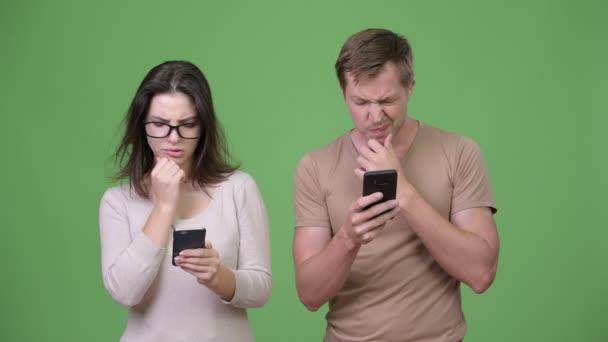 Mladý pár myšlení při používání telefonu dohromady