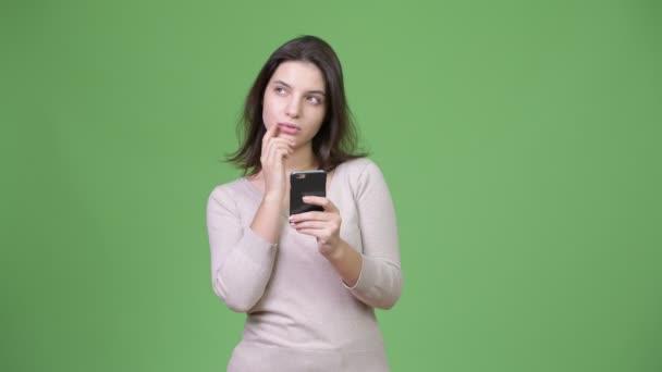 junge glückliche schöne Frau telefoniert und denkt vor grünem Hintergrund