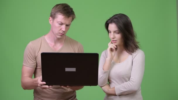 Young couple using laptop and thinking together