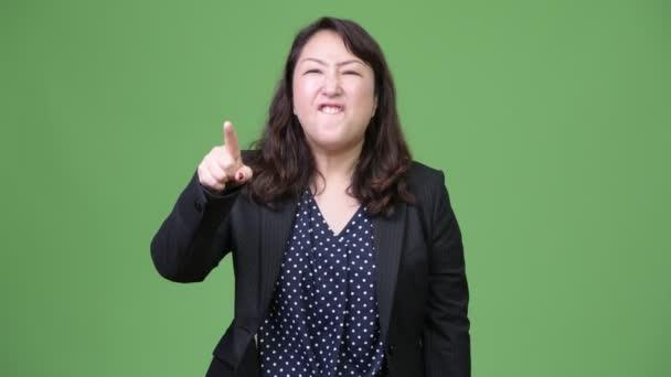 Zralé rozzlobený asijské podnikatelka ukazující na kameru křik