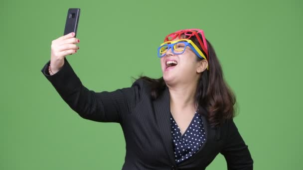 Mature beautiful Asian businesswoman using phone while wearing many eyeglasses as funny concept